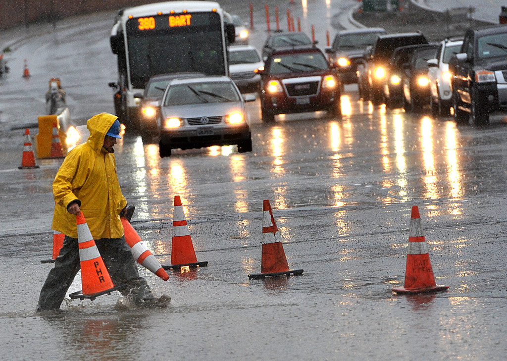 . A Caltrans worker puts down cones around a flooded area at the A Street off ramp as heavy rains and winds cause problems in Antioch, Calif., on Thursday, Dec. 11, 2014.  (Dan Rosenstrauch/Bay Area News Group)