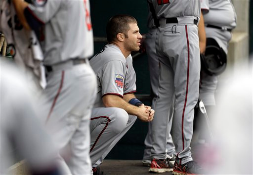 . Minnesota Twins\' Joe Mauer watches from the dugout against the Detroit Tigers in the first inning of a baseball game in Detroit, Friday, June 13, 2014.  (AP Photo/Paul Sancya)