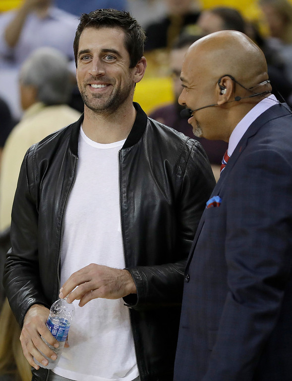 . Green Bay Packers quarterback Aaron Rodgers, left, laughs with Michael Wilbon before Game 5 of basketball\'s NBA Finals between the Golden State Warriors and the Cleveland Cavaliers in Oakland, Calif., Monday, June 12, 2017. (AP Photo/Marcio Jose Sanchez)