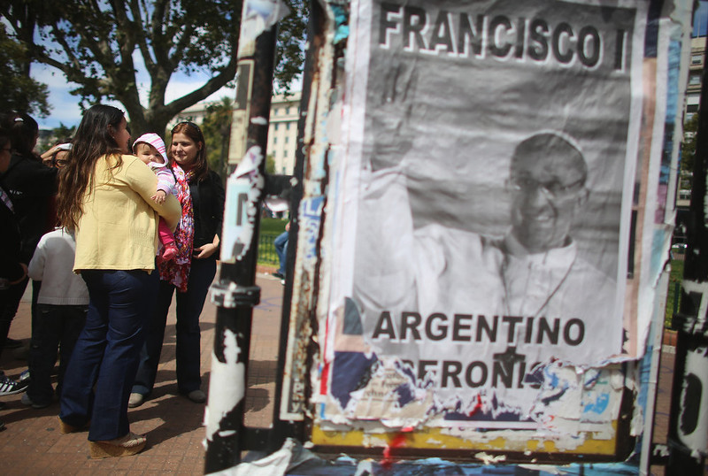 . People stand next to an image of Pope Francis following Sunday Mass outside the Metropolitan Cathedral on March 17, 2013 in Buenos Aires, Argentina. Francis was the archbishop of Buenos Aires and is the first Pope to hail from South America.  (Photo by Mario Tama/Getty Images)