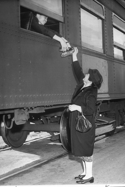 """""""Although lunches were provided for Japs who left by train, friends and relatives passed a great deal of food-stuffs through windows.  Here go two bottles of soda pop.""""--caption on photograph"""
