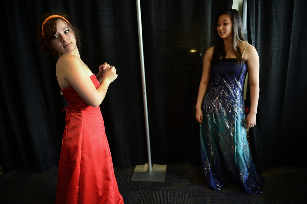 """. COMMERCE CITY, CO. - MARCH 16:  Raven Gereaux, left, and Allison Okita, both seniors at Legacy High School, try on dresses during the Prom Dress Exchange Corp. event in Commerce City, CO March 16, 2013. With a valid student ID and a suggested $10 donation, teenage girls could chose from 1,356 donated dresses that lined a long hallway at Dick�s Sporting Goods Park. Gereaux said, \""""prom is so expensive already, I think it\'s a great opportunity for girls to get a really nice dress for a reasonable price.\"""" (Photo By Craig F. Walker/The Denver Post)"""