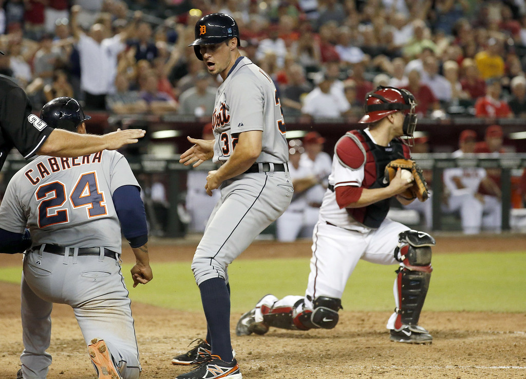 . Detroit Tigers\' Don Kelly (32) celebrates his run scored with teammate Miguel Cabrera (24) as Arizona Diamondbacks\' Miguel Montero, right, holds onto the ball during the eighth inning of a baseball game on Tuesday, July 22, 2014, in Phoenix. (AP Photo)
