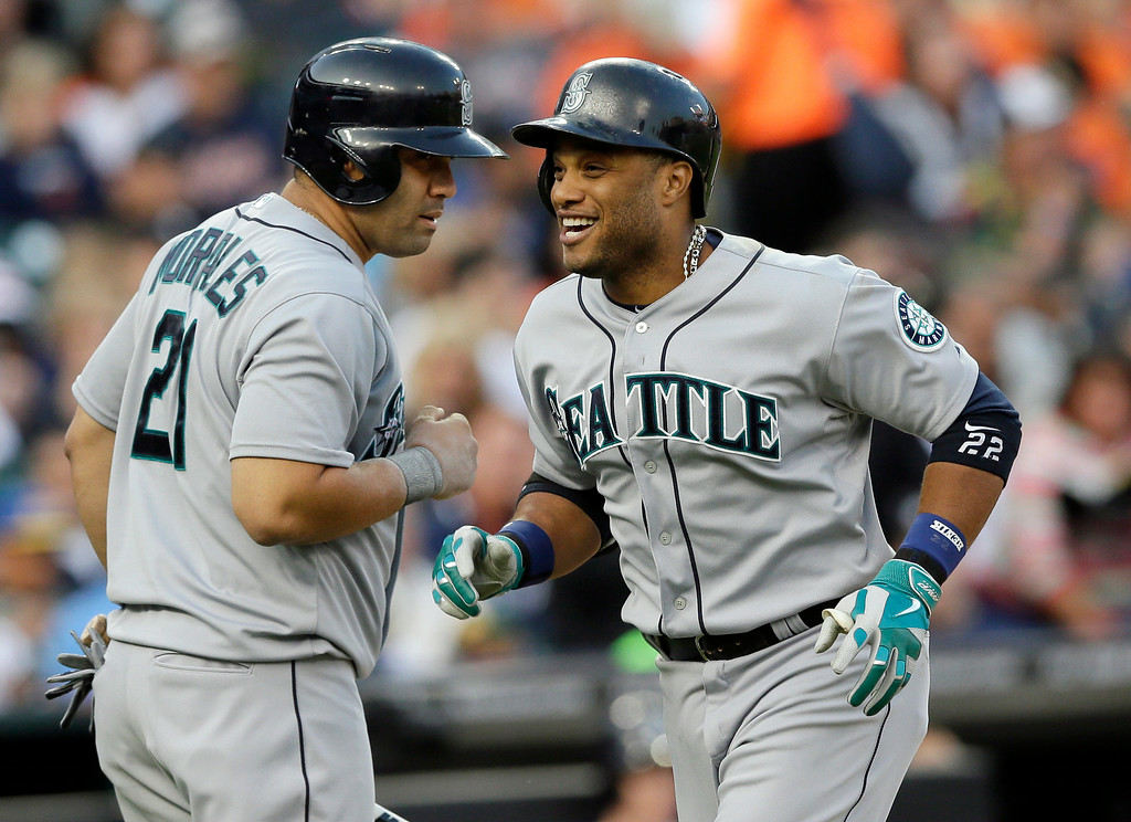 . Seattle Mariners\' Robinson Cano, right, is congratulated by teammate Kendrys Morales after his solo home run during the third inning of a baseball game against the Detroit Tigers, Friday, Aug. 15, 2014, in Detroit. (AP Photo/Carlos Osorio)