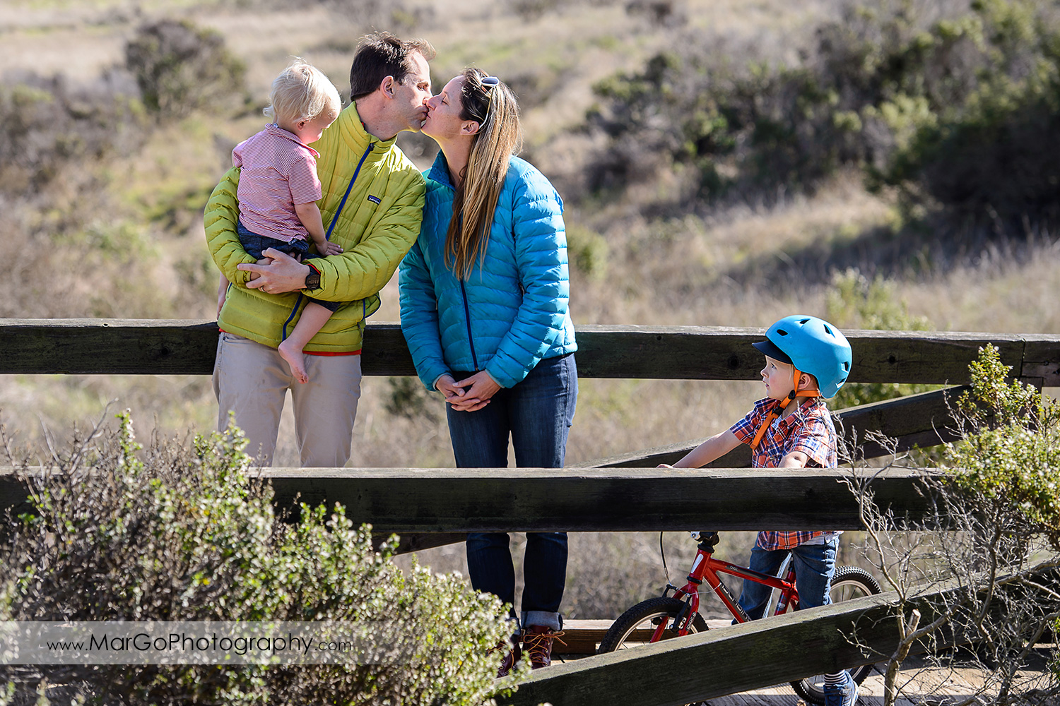 two young boys looking at mom and dad kissing during outdoor family session at San Raeael China Camp SP