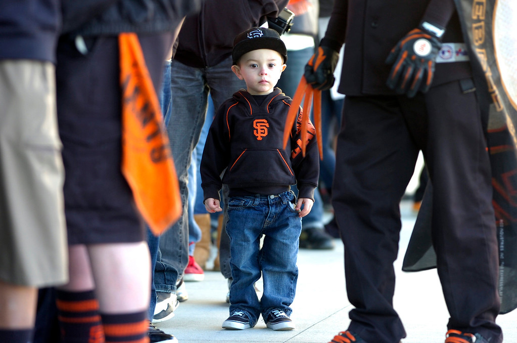 . Anthony Nicoli, 2, checks out the claws on Erik Lopez\'s Giants Wolverine outfit as he waits in line with his grandfather to see the World Series Trophy as it makes a stop at the Richmond Memorial Auditorium in Richmond, Calif. on Monday, Jan. 14, 2013.  (Kristopher Skinner/Staff)