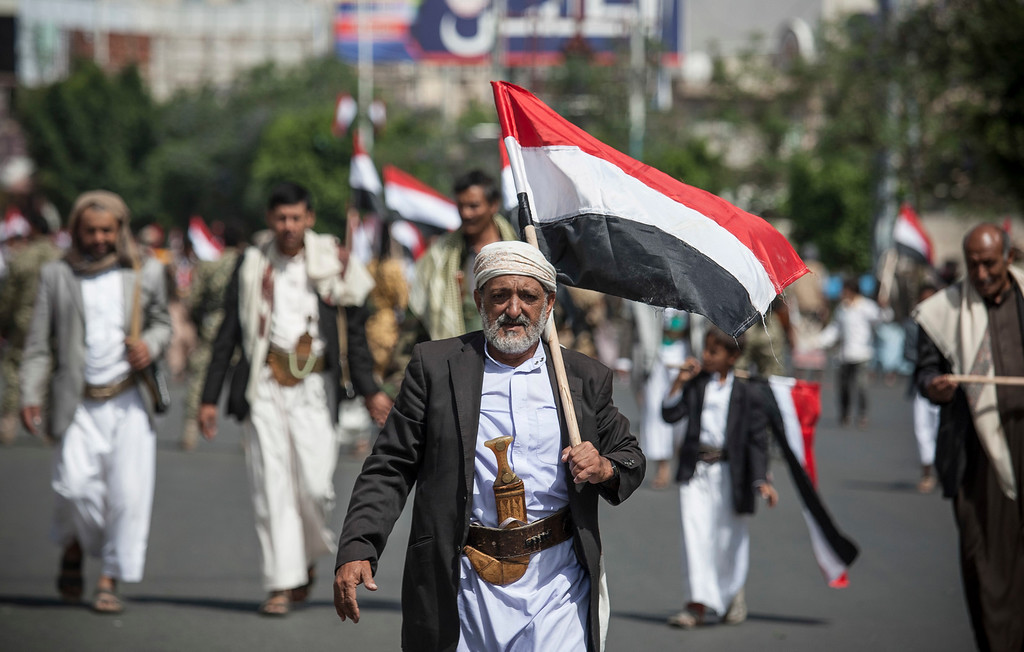 . A man holds Yemen\'s flag during a ceremony to commemorate the 26th anniversary of Yemen\'s reunification, in Sanaa, Yemen, Sunday, May 22, 2016. South and North Yemen were independent states until unification in 1990. (AP Photo/Hani Mohammed)