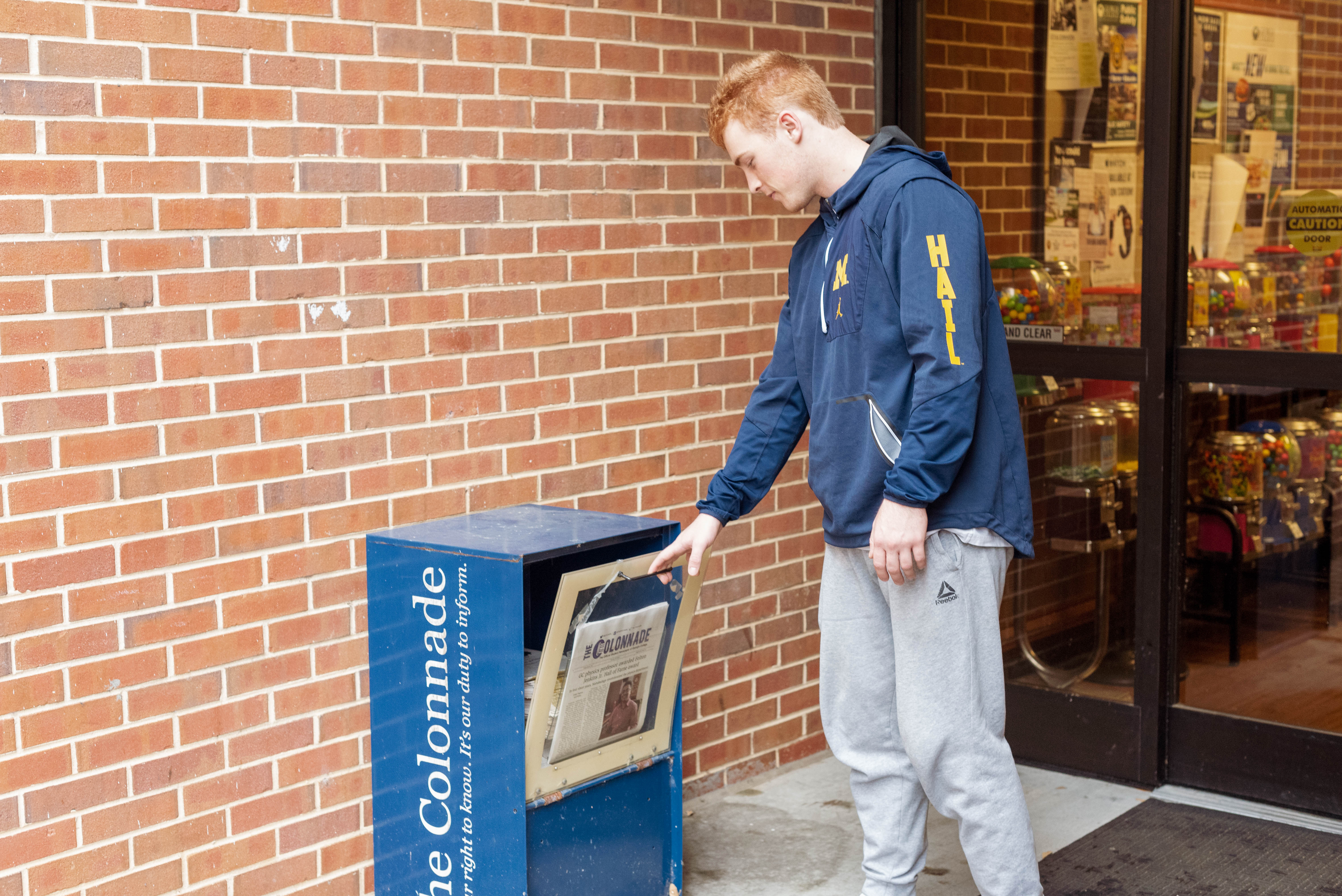 Eric Boyd places copies into a newspaper bin outside of the Maxwell Student Union