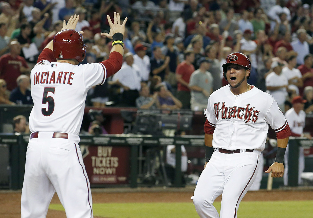 . Arizona Diamondbacks\' Ender Inciarte (5) and David Peralta, right, celebrate their runs scored against the Detroit Tigers during the eighth inning of a baseball game on Tuesday, July 22, 2014, in Phoenix. The Diamondbacks won 5-4. (AP Photo)