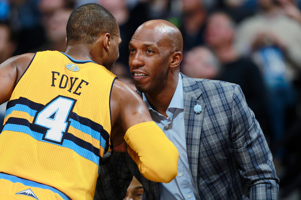 . Injured Detroit Pistons guard Chauncey Billups, right, greets Denver Nuggets guard Randy Foye in the third quarter of the Nuggets\' 118-109 victory in an NBA basketball game in Denver on Wednesday, March 19, 2014. (AP Photo/David Zalubowski)