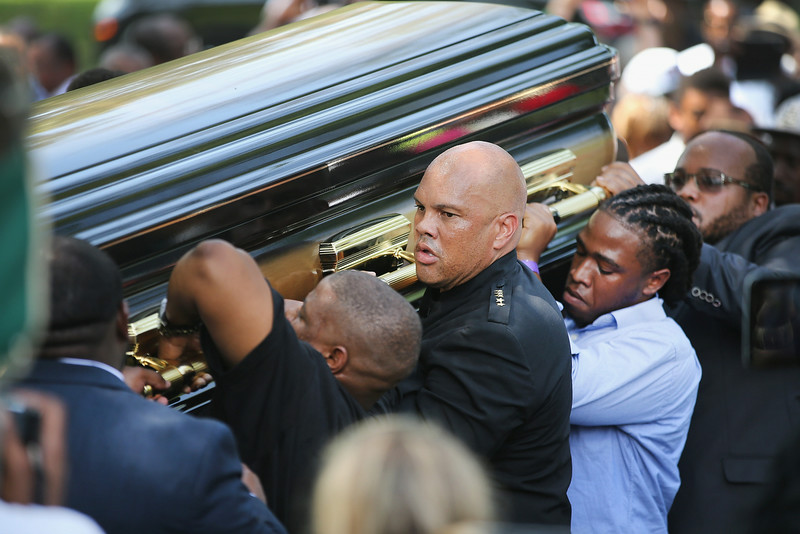 . Pallbearers carry the remains of Michael Brown at Saint Peters Cemetery for burial on August 25, 2014 in St. Louis, Missouri. Michael Brown, an 18 year-old unarmed teenager, was shot and killed by Ferguson Police Officer Darren Wilson in the nearby town of Ferguson, Missouri on August 9. His death caused several days of violent protests along with rioting and looting in Ferguson.  (Photo by Scott Olson/Getty Images)