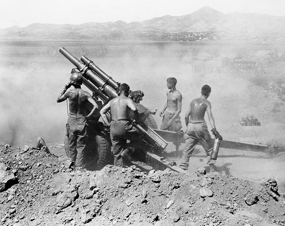 . Gun crew of the 25th Infantry Division fire a 105 mm howitzer on North Korean positions near Uirson, in Korea on August 27, 1950. (AP Photo)