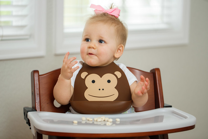 Make_My_Day_Bib_Lifestyle_Monkey_Girl_In_Highchair_Looking_Left_Hands_Up.JPG