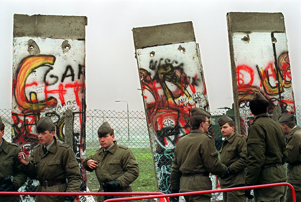 . East German border guards demolishing a section of the Berlin wall in order to open a new crossing point between East and West Berlin, 11 November 1989 at the border line near the Potsdamer Square. (Photo credit GERARD MALIE/AFP/Getty Images)