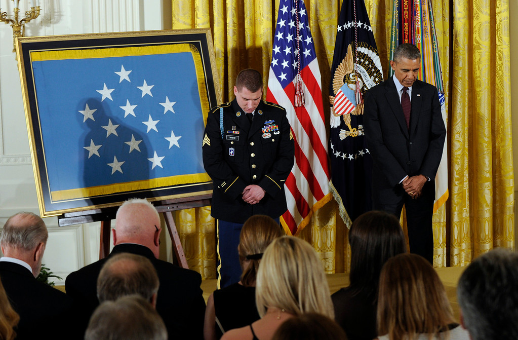 . President Barack Obama and Army Sgt. Kyle J. White bow their heads in prayer at the start of a ceremony  in the East Room of the White House in Washington, Tuesday, May 13, 2014, where White was awarded the Medal of Honor.  (AP Photo)