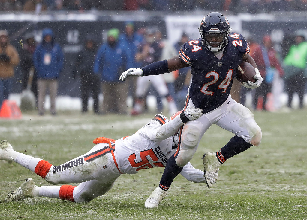 . Chicago Bears running back Jordan Howard (24) tries to elude Cleveland Browns outside linebacker James Burgess (52) in the second half of an NFL football game in Chicago, Sunday, Dec. 24, 2017. (AP Photo/Charles Rex Arbogast)