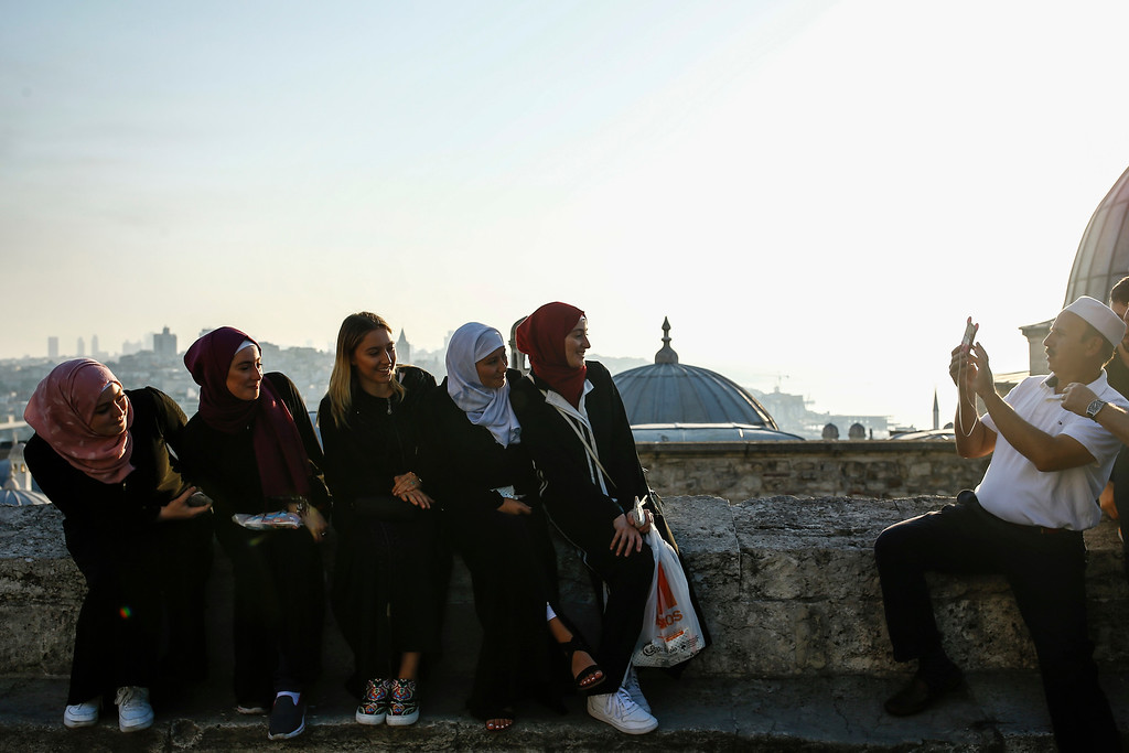 . Backdropped by Istanbul\'s skyline, people enjoy the first day of Eid al-Fitr, which marks the end of the holy fasting month of Ramadan, early Friday, June 15, 2018. (AP Photo/Emrah Gurel)