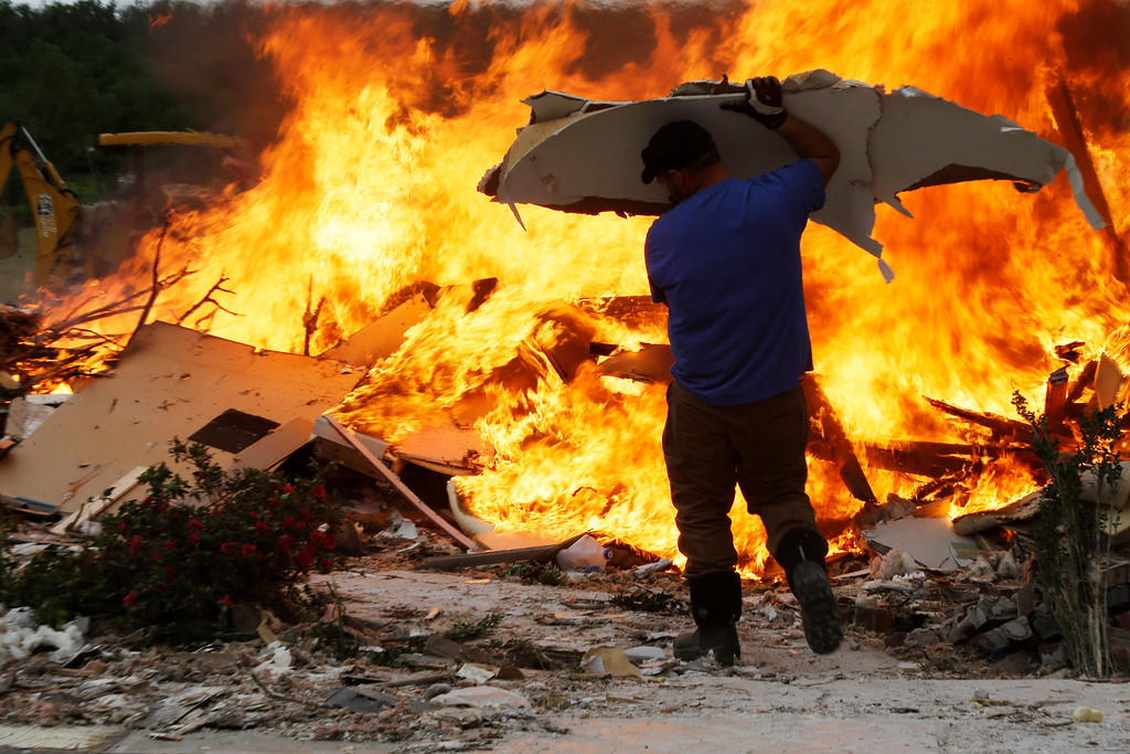 . A volunteer throws debris from a destroyed house onto a fire in Vilonia, Ark., Wednesday, April 30, 2014. A tornado struck the town late Sunday.  Along stretches of damaged houses, volunteers with chain saws cleared trees from across homes, driveways and streets.  (AP Photo/Danny Johnston)