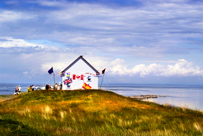 White house with colorful flags on a grassy hill, Saturna Island, BC.