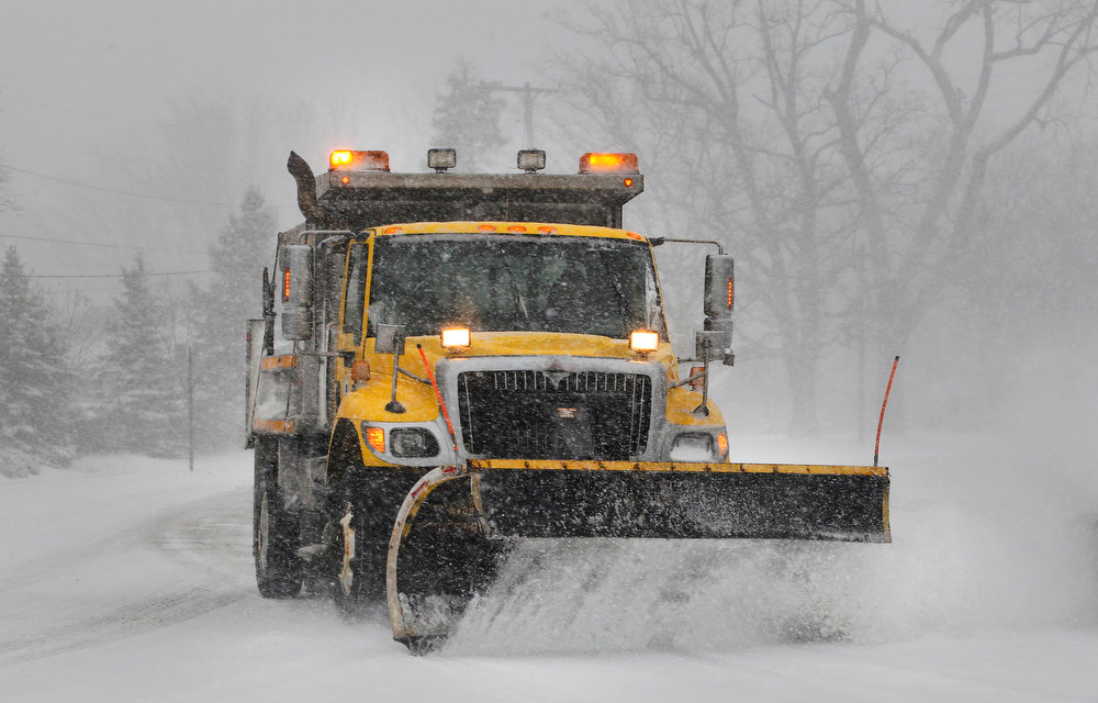 . A snowplow clears Happy Hollow Road at the intersection with Soldier\'s Home Road Wednesday, Dec. 26, 2012, in West Lafayette, Ind. (AP Photo/Journal & Courier, John Terhune)