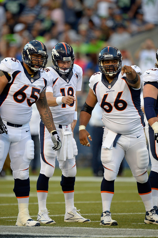 . SEATTLE, WA. - AUGUST 17: Denver Broncos offensive guard Justin Boren (65) looks on as Manny Ramirez (66) points out the defense with Peyton Manning (18) during the first quarter agains the  Seattle Seahawks August 17, 2013 at Century Link Field. (Photo By John Leyba/The Denver Post)