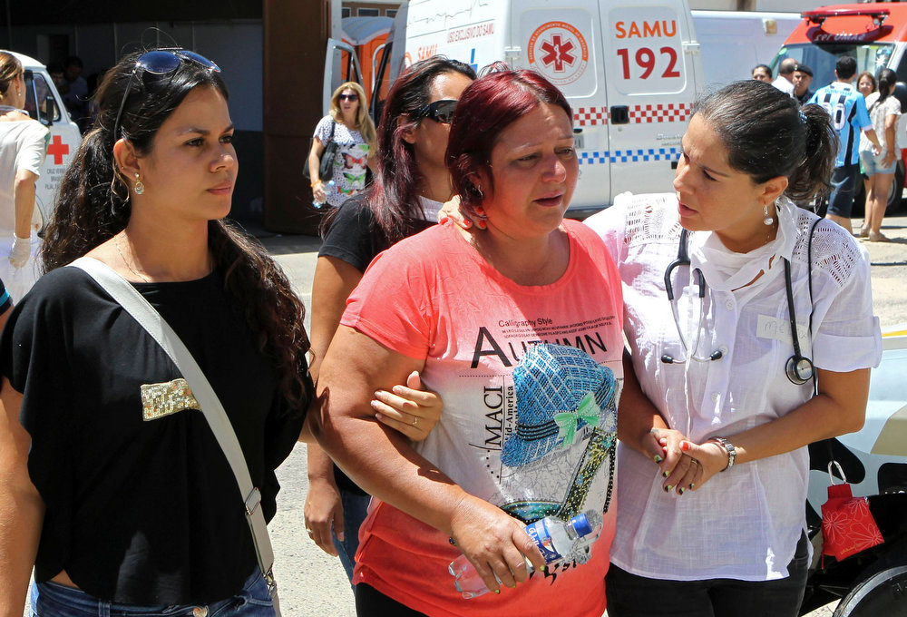 ". Relatives are helped by a healthcare worker after identifying the body of a victim of the fire at Boate Kiss nightclub in the southern city of Santa Maria, 187 miles (301 km) west of the state capital of Porto Alegre, January 27, 2013. A fire in a nightclub killed at least 245 people in southern Brazil on Sunday when a band\'s pyrotechnics show set the building ablaze and fleeing patrons were unable to find the emergency exits in the ensuing panic, officials said. The blaze in the southern city of Santa Maria was started when a band member or someone from its production team ignited a flare, which then set fire to the ceiling, said Luiza Sousa, a civil police official. The fire spread ""in seconds,\"" she said. An estimated 500 people were in the Boate Kiss nightclub when the fire broke out early on Sunday, and many were unable to find the exits as dark smoke quickly filled the room. At least one exit was locked, trapping hundreds inside to die, many from asphyxiation as they inhaled smoke, police said. REUTERS/Edison Vara"