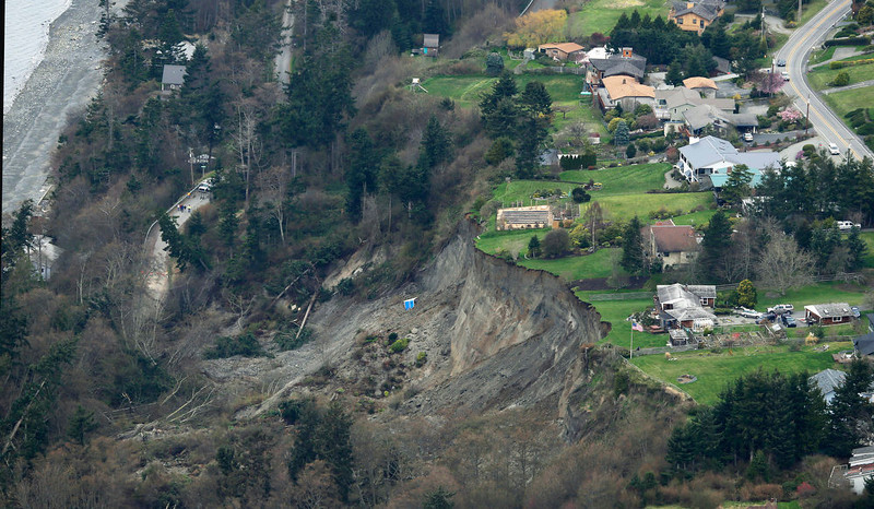 . This aerial photo shows a landslide near Coupeville, Wash. on Whidbey Island, Wednesday, March 27, 2013. The slide severely damaged one home and isolated or threatened more than 30 on the island, about 50 miles north of Seattle in Puget Sound. No one was reported injured in the slide, which happened at about 4 a.m. Wednesday. (AP Photo/Ted S. Warren)