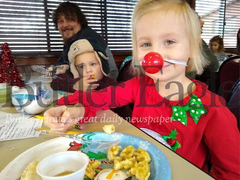 Eliza Clark, 4, enjoys the Breakfast with Santa Saturday, Dec. 7, 2019, at the Butler Township Park  building. The event was sponsored by the Butler County Parks and Recreation. Beside Eliza is her brother, Blake, 3, and father Justin, all of Butler. Also attending was the children's mother, Jen, and their aunt and uncle, Lynsey and Travis Frenchak. Donna Sybert/Butler Eagle