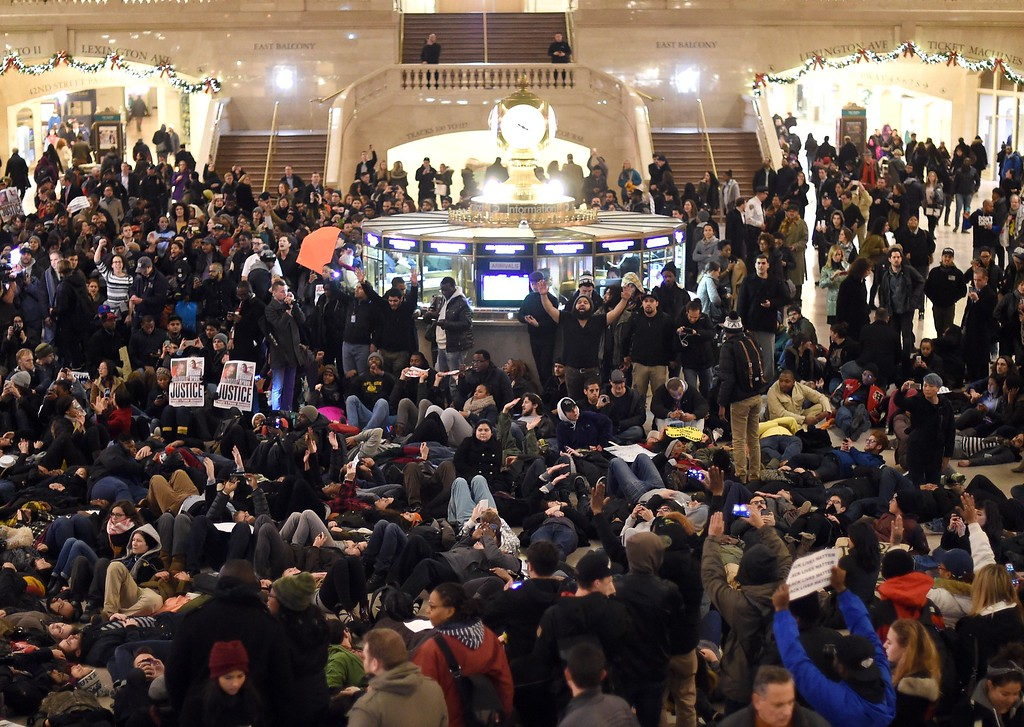 . Protestors lay down in Grand Central Station during a protest on December 3, 2014 after a grand jury decided not to charge a white police officer in the choking death of Eric Garner, a black man, days after a similar decision sparked renewed unrest in Missouri. Eric Garner died after being placed in a chokehold by New York police Officer Daniel Pantaleo while being arrested on suspicion of selling untaxed cigarettes in Staten Island. AFP PHOTO / Timothy A. CLARY/AFP/Getty Images