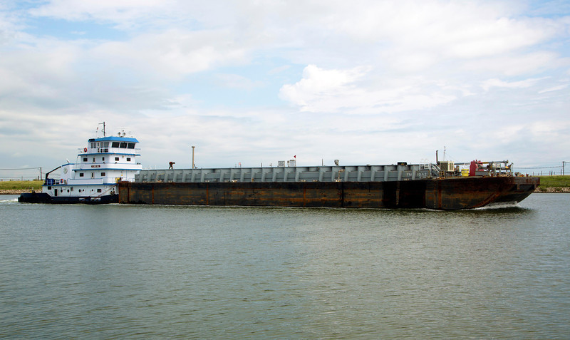 The Cindy Hill Pushboat drives a large barge past the Ferrel.