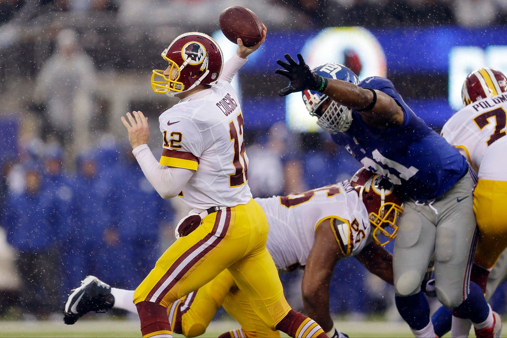 . Washington Redskins quarterback Kirk Cousins (12) throws a pass as teammate Chris Chester (66) blocks New York Giants\' Justin Tuck (91) during the first half of an NFL football game on Sunday, Dec. 29, 2013, in East Rutherford, N.J.  (AP Photo/Julio Cortez)