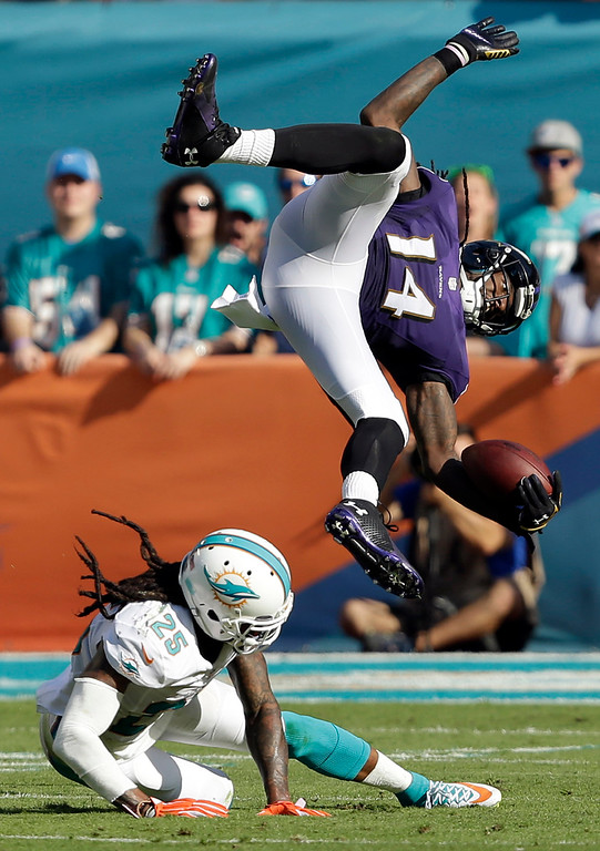 . Baltimore Ravens wide receiver Marlon Brown (14) trips over Miami Dolphins free safety Louis Delmas (25) during the second half of an NFL football game, Sunday, Dec. 7, 2014, in Miami Gardens, Fla. (AP Photo/Wilfredo Lee)