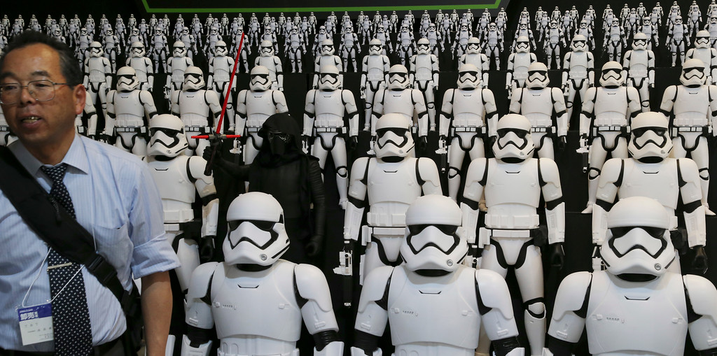". A man stands in front of figures from ""Star Wars\"" at the International Tokyo toy show in Tokyo, Friday, June 10, 2016. The show goes from June 9 until June 12, 2016.  (AP Photo/Koji Sasahara)"