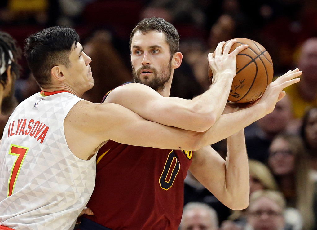 . Cleveland Cavaliers\' Kevin Love, right, looks to pass against Atlanta Hawks\' Ersan Ilyasova (7), from Turkey, in the first half of an NBA basketball game, Tuesday, Dec. 12, 2017, in Cleveland. (AP Photo/Tony Dejak)
