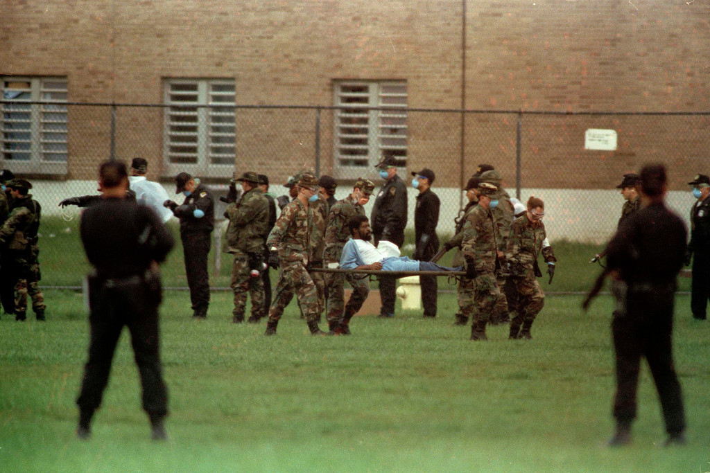 . An injured inmate is carried on a stretcher from the cell block at the Southern Ohio Correctional Facility in Lucasville, Ohio, April 21, 1993, where 450 inmates have barricaded themselves since Easter Sunday.  The inmates and prison officials agreed Wednesday to end the siege that has killed one guard and seven inmates.  (AP Photo/Lennox McLendon)
