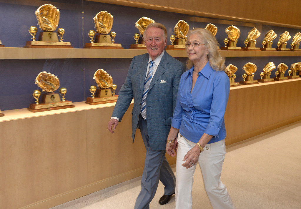 . File - Vin Scully and his wife Sandy Scully walk down the hall after holding a press conference at Dodger Stadium. Scully, a Hall of Fame broadcaster, will return to the Dodger broadcast booth for an unprecedented 66th season in 2015. The announcement was made by several Dodger players on Dodger Vision during last night�s game against the Atlanta Braves. Los Angeles, CA. 7/30/2014 (Photo by John McCoy Daily News)