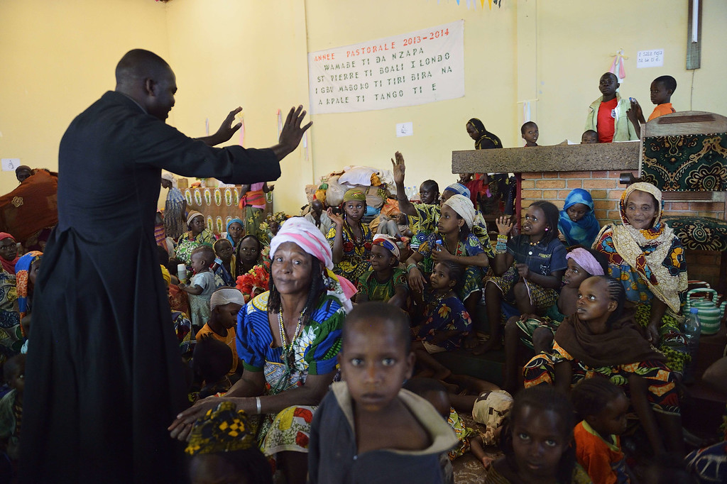 . Priest Xavier Arnold Fagba comforts Muslim people taking refuge in the Boali church on January 19, 2014, in Boali, some 100km north of Bangui. Fresh fighting broke out in the strife-torn Central African Republic on the eve of an announcement of the candidates seeking to become the new interim president. Sectarian violence has gripped the landlocked country after a March 2013 coup launched by the mostly Muslim Seleka rebels, and the UN has warned that the bloodshed could turn into genocide. AFP  PHOTO / ERIC FEFERBERG/AFP/Getty Images