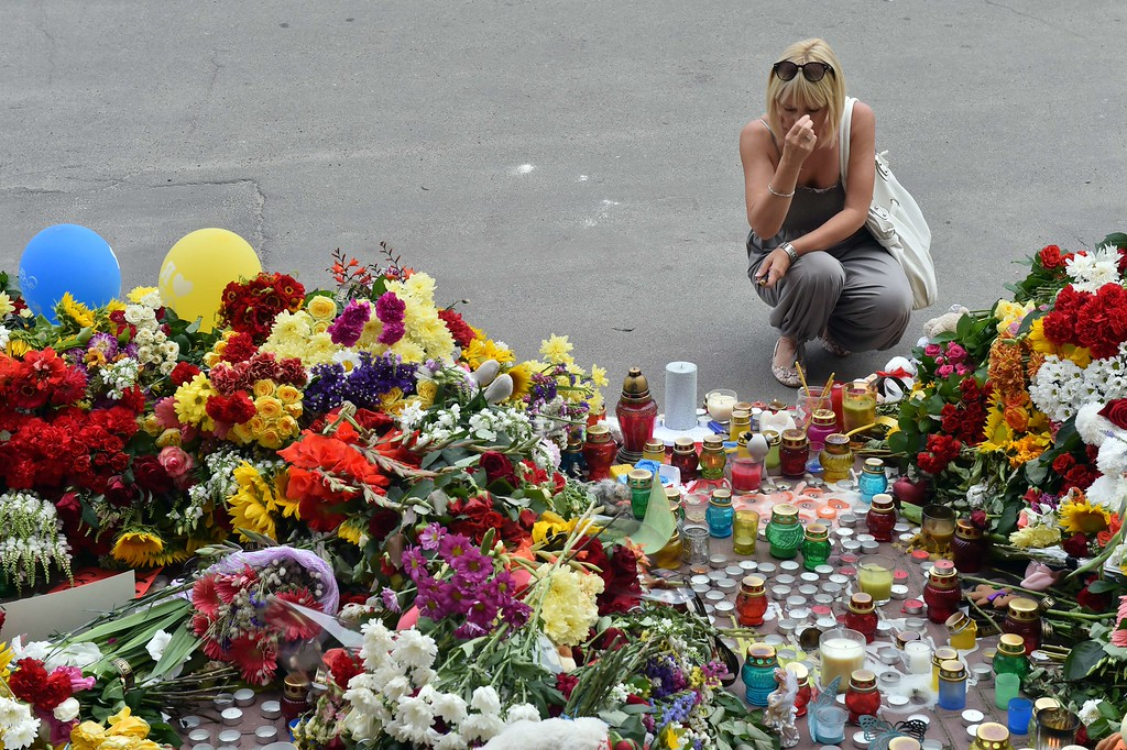 . A woman crosses herself as people lay flowers and light candles in front of the Embassy of the Netherlands in Kiev on July 18, 2014, to commemorate passengers of Malaysian Airlines flight MH17 carrying 295 people from Amsterdam to Kuala Lumpur which crashed in eastern Ukraine.  Ukraine\'s prime minister said Friday that pro-Russian separatist rebels that Kiev believes shot down a Malaysian airliner with 298 people on board should face an international tribunal in The Hague. AFP PHOTO/ SERGEI SUPINSKY/AFP/Getty Images