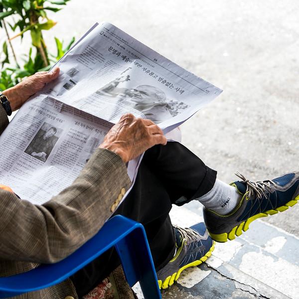Elderly man reading newspaper, Seoul, South Korea