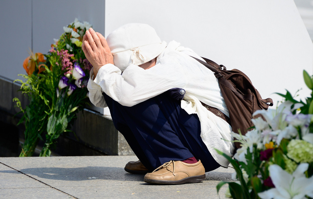 . An elderly woman prays for victims of the 1945 atomic bombing of Hiroshima in front of the cenotaph at the Peace Memorial Park in Hiroshima on August 5, 2013. Hiroshima is marking the 68th anniversary of the atomic bombing on August 6, 2013.         AFP PHOTO/Toru  YAMANAKA/AFP/Getty Images