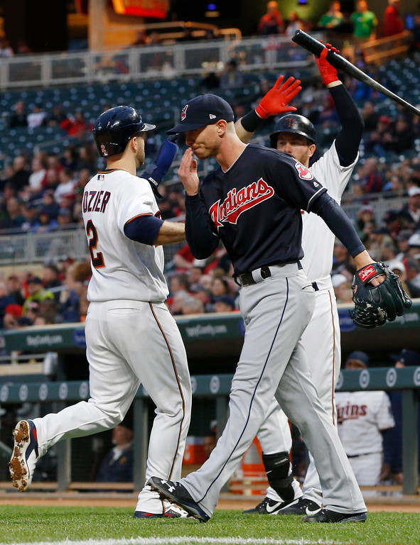 . Minnesota Twins\' Brian Dozier, left, is welcomed by Robbie Grossman after scoring on a Max Kepler sacrifice fly off Cleveland Indians pitcher Josh Tomlin, right, front, during the first inning of a baseball game Tuesday, April 18, 2017, in Minneapolis. (AP Photo/Jim Mone)