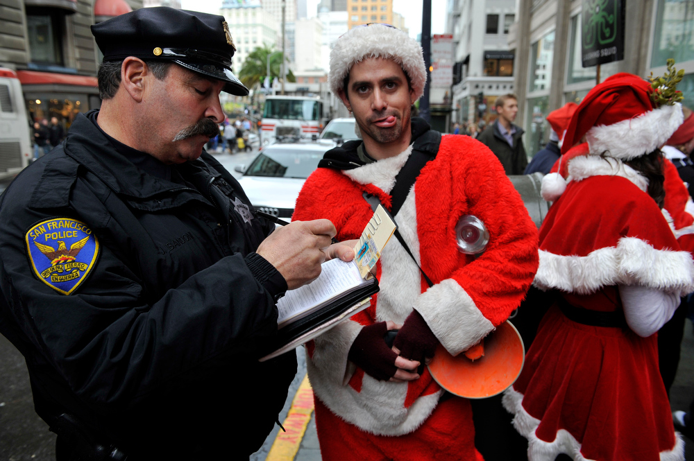 Description of . This Dec. 10, 2009 file photo shows a San Francisco Police officer giving a man dressed as Santa Claus an open container ticket during the Santacon pub crawl in downtown San Francisco.  SantaCon is coming to town _ in fact, to nearly 300 towns and cities around the world. Dozens, sometimes hundreds of red-suited revelers gather, bar hop, stop traffic and pose for photos.   (AP Photo/Russel A. Daniels, file)