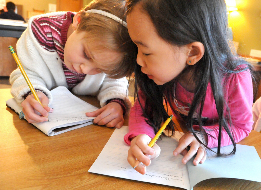 . Students Althea Lo, right, and Ella and work together on their daily journals. (Pioneer Press: John Doman)