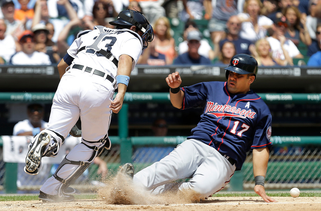 . Minnesota Twins\' Kendrys Morales (17) slides safely into home plate on a Kurt Suzuki single as Detroit Tigers catcher Alex Avila (13) chases down the throw that bounced off him in the sixth inning of a baseball game in Detroit, Sunday, June 15, 2014. (AP Photo/Paul Sancya)