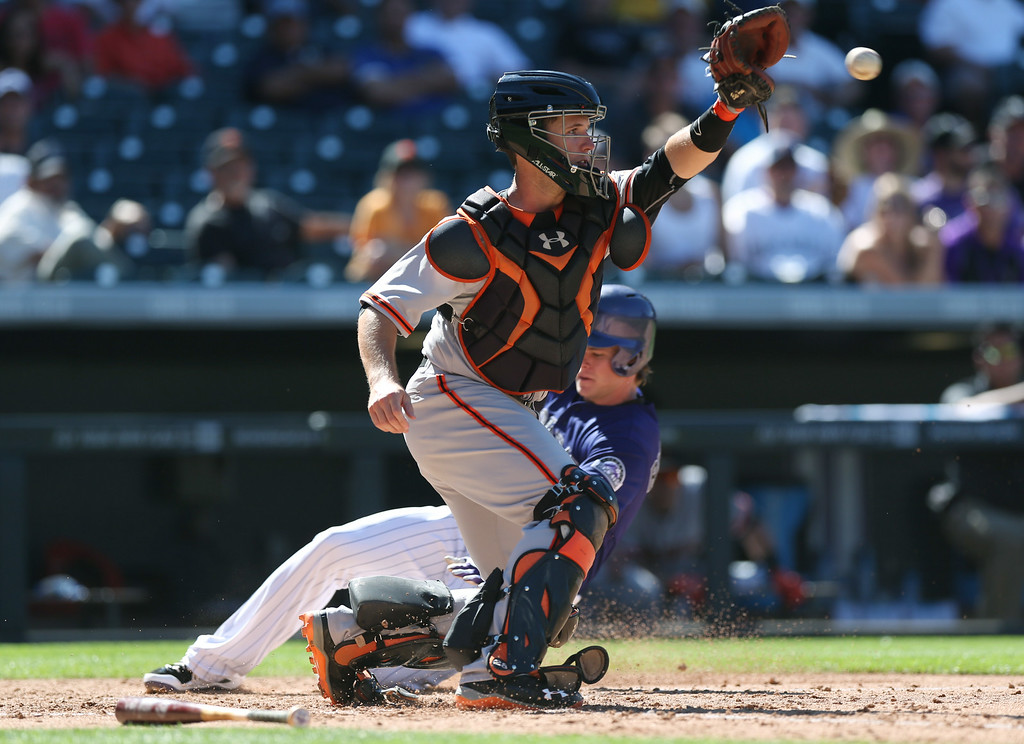 . San Francisco Giants catcher Buster Posey, front, fields throw as Colorado Rockies\' Josh Rutledge scores on a sacrifice fly hit by Justin Morneau in the sixth inning of a baseball game in Denver, Wednesday, Sept. 3, 2014. The Rockies won 9-2. (AP Photo/David Zalubowski)