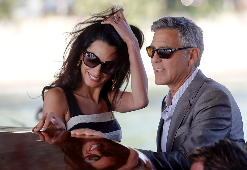 . George Clooney, left, and his fiancee Amal Alamuddin arrive in Venice, Italy, Friday, Sept. 26, 2014. Clooney, 53, and Alamuddin, 36, are expected to get married this weekend in Venice, one of the worldís most romantic settings. (AP Photo/Luca Bruno)