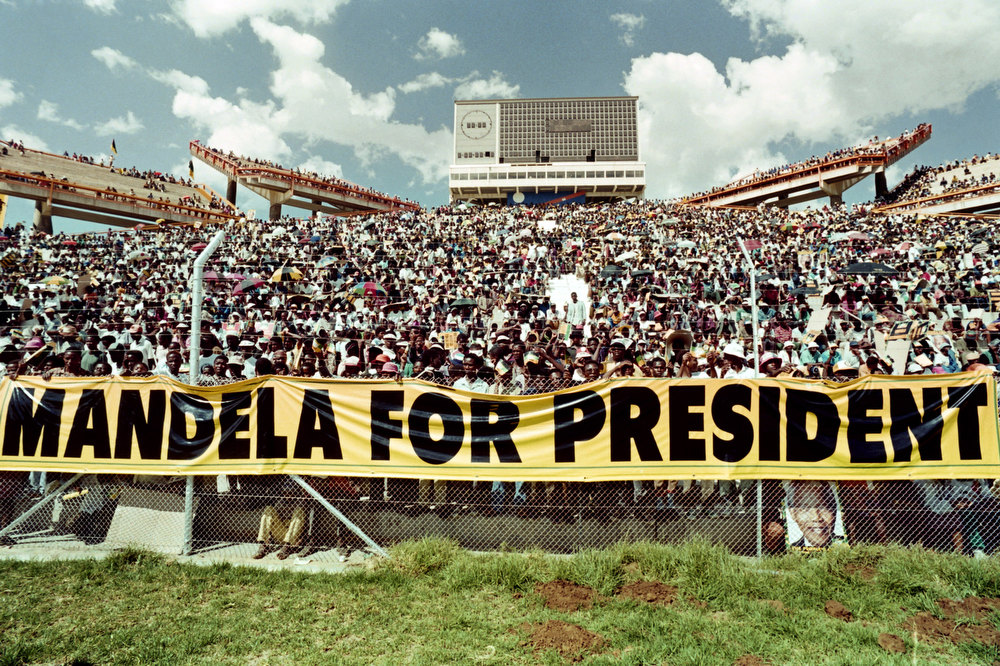 Description of . A crowd of estimated 40.000 African National Congress (ANC) supporters listen to the address of ANC President Nelson Mandela during a mass rally in Mmabatho 15 March 1994 prior to the 27 April general election. South Africans will vote 27 April 1994 in the country's first democratic and multiracial general elections. Mmabatho Stadium is a multi-purpose stadium in Mafikeng, South Africa. It is currently used mostly for football matches. The stadium holds 59,000 people and was designed and built in 1981 by a Russian construction firm. The South African general election of 1994 was an election held in South Africa to mark the end of apartheid, therefore also the first held with universal adult suffrage.  AFP PHOTO WALTER DHLADHLA (Photo credit should read WALTER DHLADHLA/AFP/Getty Images)