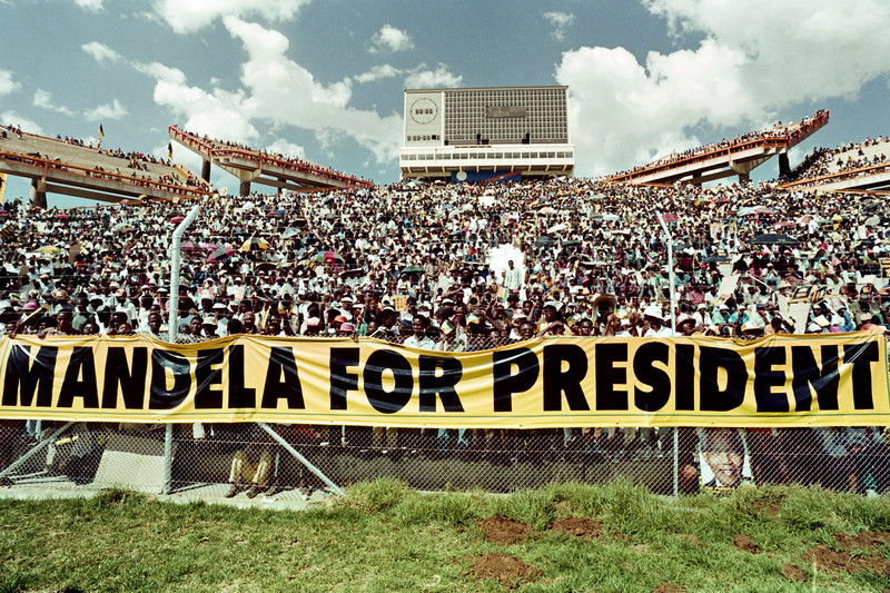 . A crowd of estimated 40.000 African National Congress (ANC) supporters listen to the address of ANC President Nelson Mandela during a mass rally in Mmabatho 15 March 1994 prior to the 27 April general election. South Africans will vote 27 April 1994 in the country\'s first democratic and multiracial general elections. Mmabatho Stadium is a multi-purpose stadium in Mafikeng, South Africa. It is currently used mostly for football matches. The stadium holds 59,000 people and was designed and built in 1981 by a Russian construction firm. The South African general election of 1994 was an election held in South Africa to mark the end of apartheid, therefore also the first held with universal adult suffrage.  AFP PHOTO WALTER DHLADHLA (Photo credit should read WALTER DHLADHLA/AFP/Getty Images)