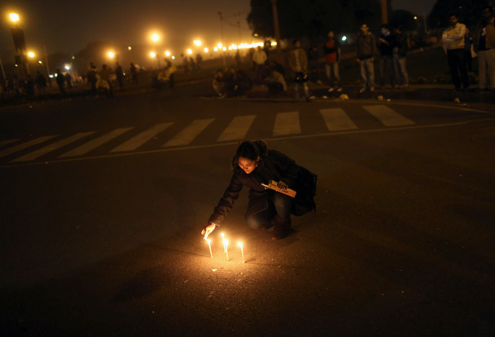 Description of . A demonstrator lights candles near the presidential palace during a protest rally in New Delhi December 22, 2012. Indian police used batons, tear gas and water cannon to turn back thousands of people marching on the presidential palace on Saturday in intensifying protests against the gang-rape of a woman on the streets and on social media. REUTERS/Adnan Abidi