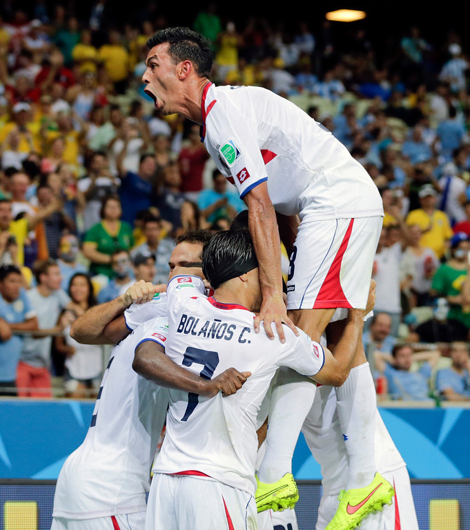 . Costa Rican players celebrate a goal by Marco Urena during the group D World Cup soccer match between Uruguay and Costa Rica at the Arena Castelao in Fortaleza, Brazil, Saturday, June 14, 2014.  (AP Photo/Fernando Llano)